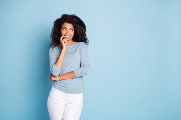 Foto van vrolijk schattig aardig mooi meisje nagels bijten op zoek naar lege ruimte planning haar sluwe idee in witte broek broek geïsoleerd pastel kleur achtergrond
