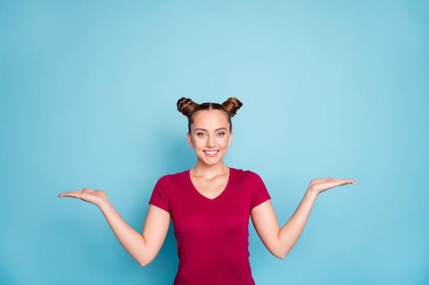Foto van vrolijk schattig lief mooi charmant meisje dat twee voorwerpen met handen vasthoudt die je twee kanten van een probleem laten zien dat moet worden opgelost, gekleed in een rood t-shirt geïsoleerd over een blauwe pastelkleurige muur