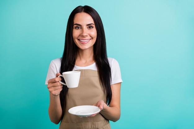 Foto van vrolijk schattig vrij aardig meisje werkt als server in restaurant glimlachend toothily in de buurt van lege ruimte geïsoleerde levendige blauwgroen kleur achtergrond