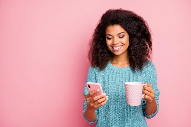 Foto van vrolijk toothy stralend schattig meisje dat door telefoon bladert die blauwe sweater met in hand kop dragen geïsoleerde pastelkleurmuur