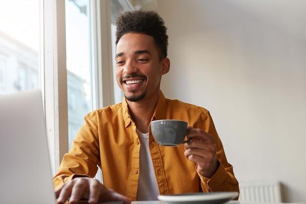 Foto van vrolijke afro-amerikaanse gelukkige kerel, zit in een café, schrijft op een laptop zijn huistaak, drinkt aromatische koffie en geniet van het leven.