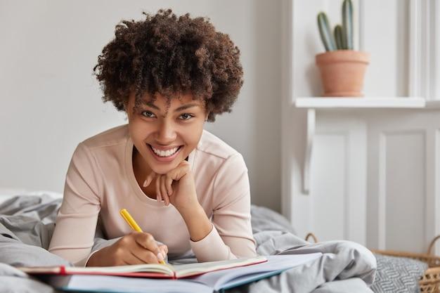 Foto van vrolijke afro-amerikaanse jongedame schrijft informatie in notitieblok met pen