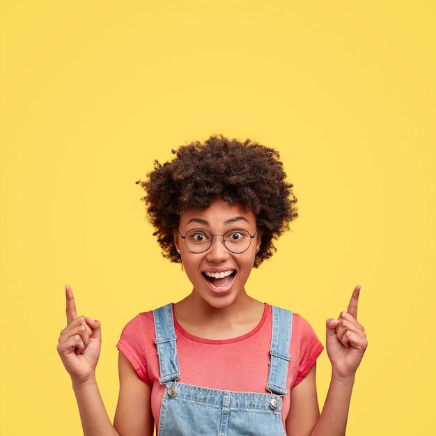 Foto van vrolijke afro-amerikaanse vrouw met positieve glimlach, knapperig haar, wijst boven met wijsvingers, heeft blije uitdrukking, poseert tegen gele muur. gelukkige donkere vrouw binnen