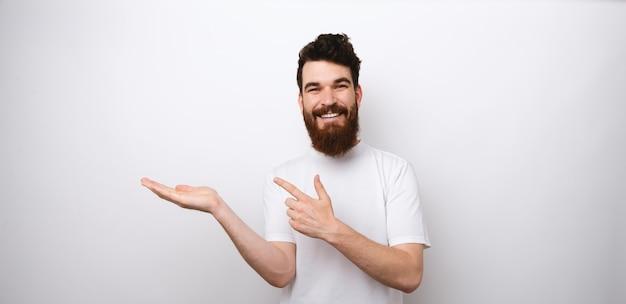 Foto van vrolijke bebaarde man in wit t-shirt wijzend op copyspace