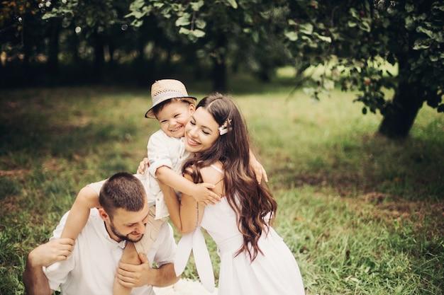 Foto van vrolijke blanke moeder, vader en hun kind hebben samen plezier en glimlachen in de tuin