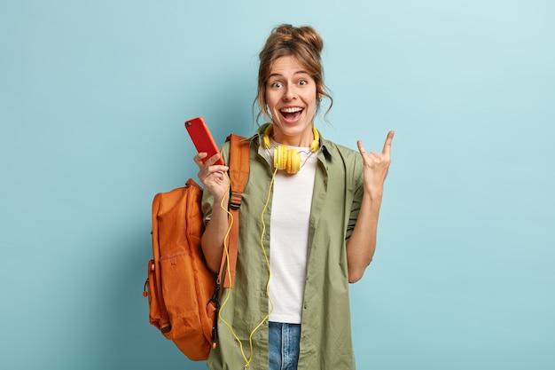 Foto van vrolijke blanke vrouw hoorn gebaar maakt, houdt slimme telefoon, luisterboek