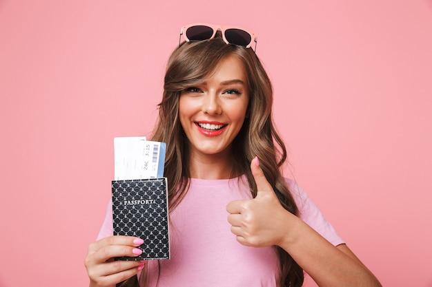 Foto van vrolijke blanke vrouw met mooi lang haar met paspoort en vliegtickets met gebaren duim omhoog, geïsoleerd op roze achtergrond