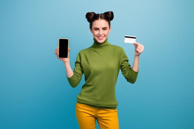 Foto van vrolijke dame houden creditcard nieuw model slimme telefoon tonen presenteren dienst online betaling dragen groene coltrui gele broek geïsoleerde blauwe kleur muur