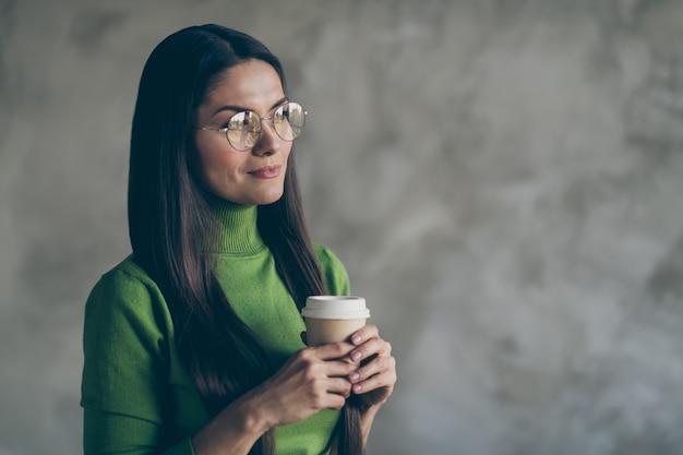 Foto van vrolijke genieten van vrouw hete koffie drinken uit papieren mok wegkijken in bril geïsoleerde grijze kleur muur betonnen achtergrond