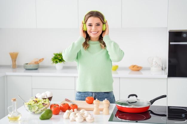 Foto van vrolijke huisvrouw die salade snijdt en smakelijk diner kookt luister muziek