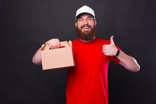 Foto van vrolijke jonge bebaarde hipster man in rood t-shirt duim opdagen en lunchdoos