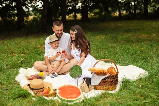 Foto van vrolijke jonge blanke vrouw en man houdt hun kind op handen, glimlacht en verheugt zich