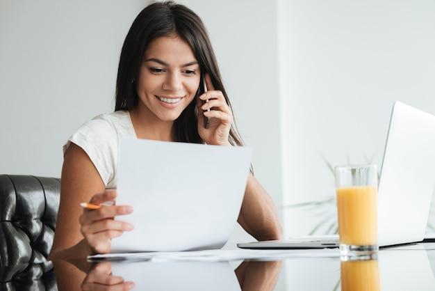 Foto van vrolijke jonge dame die laptop gebruikt en thuisfinanciën analyseert met documenten. documenten bekijken tijdens het praten via de mobiele telefoon.