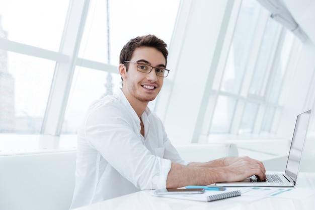 Foto van vrolijke jonge man gekleed in wit overhemd met behulp van laptopcomputer. kijk naar de camera.
