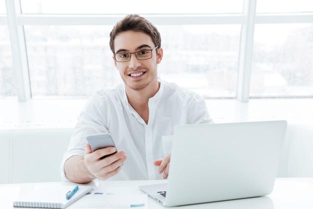 Foto van vrolijke jonge man gekleed in wit overhemd met behulp van laptopcomputer tijdens het chatten. kijk naar de camera.