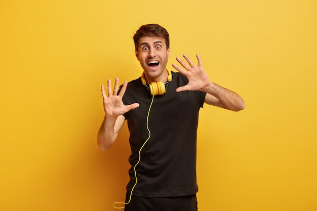 Foto van vrolijke jonge man staat met palmen gestrekt in de camera