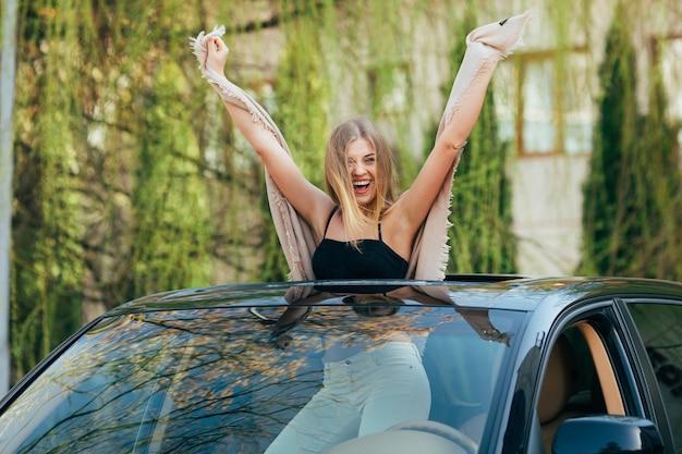 Foto van vrolijke jonge vrouw die zonnebril en opgeheven handen op het zonnedak van de luxeauto draagt