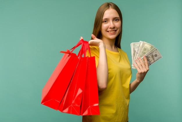 Foto van vrolijke jonge vrouw met fan van geld en rode boodschappentassen, geïsoleerd op blauw