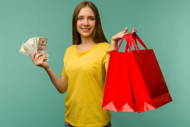 Foto van vrolijke jonge vrouw met fan van geld en rode boodschappentassen