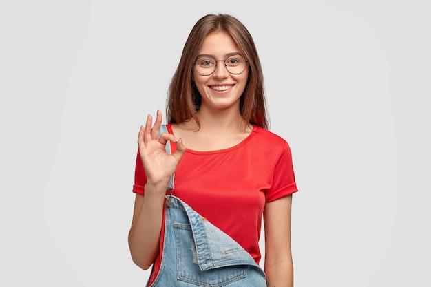 Foto van vrolijke jonge vrouw toont nul of ok gebaar, toont haar goedkeuring