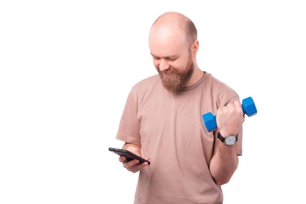 Foto van vrolijke kantoormedewerker man met behulp van smartphone en werken met blauwe halter