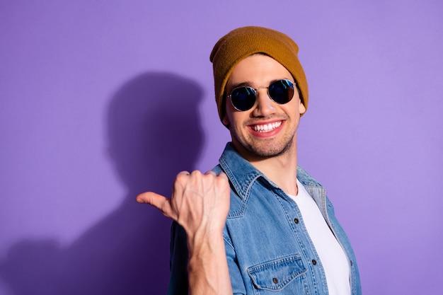 Foto van vrolijke knappe aantrekkelijke kerel die u weg toont naar het bereiken van succes het dragen van jeans spijkerjasje brillen brillen bril geïsoleerd op paarse levendige kleurenachtergrond