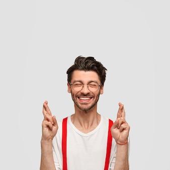 Foto van vrolijke knappe ongeschoren man met trendy kapsel kruist vingers, gelooft in iets moois, houdt de ogen gesloten, elegant gekleed, geïsoleerd over witte muur. mensen en wens concept