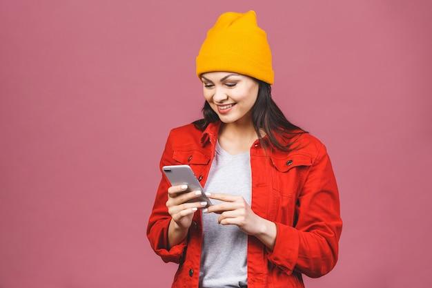 Foto van vrolijke leuke mooie jonge vrouw die door mobiele telefoon babbelt die over roze muurmuur wordt geïsoleerd.