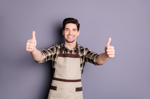 Foto van vrolijke leuke positieve knappe man smilt toothy duimen opdagen om kwaliteit geïsoleerde grijze kleur muur te benadrukken
