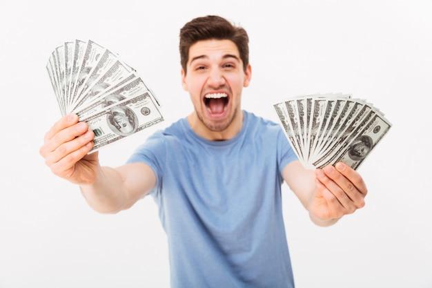 Foto van vrolijke man in casual t-shirt schreeuwen en demonstreren zijn geldprijs in contant geld op camera, geïsoleerd over witte muur
