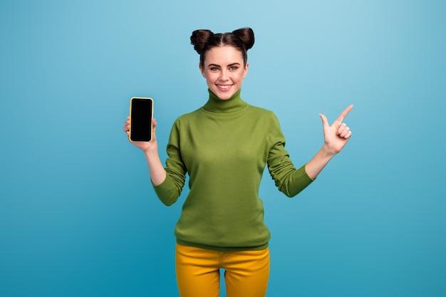Foto van vrolijke mooie dame houden nieuw model smartphone apparaat regisseren vinger zijkant lege ruimte tonen verkoop banner dragen groene coltrui gele broek geïsoleerde blauwe kleur muur