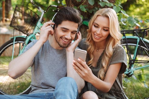 Foto van vrolijke mooie jonge paar samen zitten en het gebruik van smartphone buitenshuis