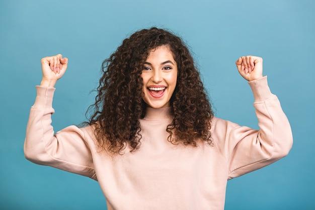 Foto van vrolijke mooie jonge vrouw geïsoleerd op blauwe muur achtergrond.