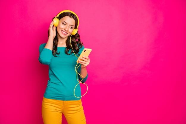 Foto van vrolijke mooie vrij schattige charmante vriendin luisteren naar muziek in haar koptelefoon met telefoon met handen geïsoleerd roze levendige kleurenachtergrond