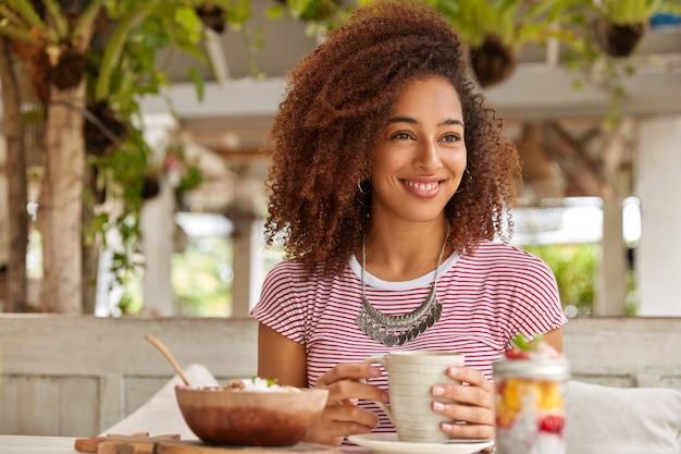 Foto van vrolijke ontspannen zwarte meid met krullend haar, mok koffie houdt, geniet van tijdverdrijf, bezoekt exotische cafetaria, zomervakantie in het buitenland heeft, kijkt opzij