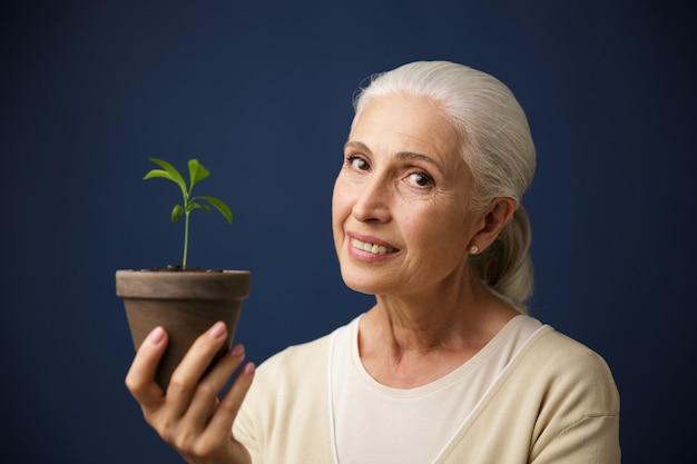 Foto van vrolijke oude vrouw die jonge plant ter plaatse houdt