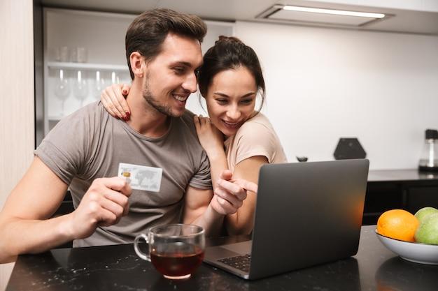 Foto van vrolijke paar man en vrouw met behulp van laptop met creditcard, zittend in de keuken