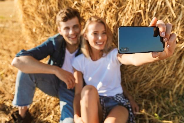 Foto van vrolijke paar man en vrouw selfie te nemen op smartphone zittend onder grote hooiberg in gouden veld, tijdens zonnige dag