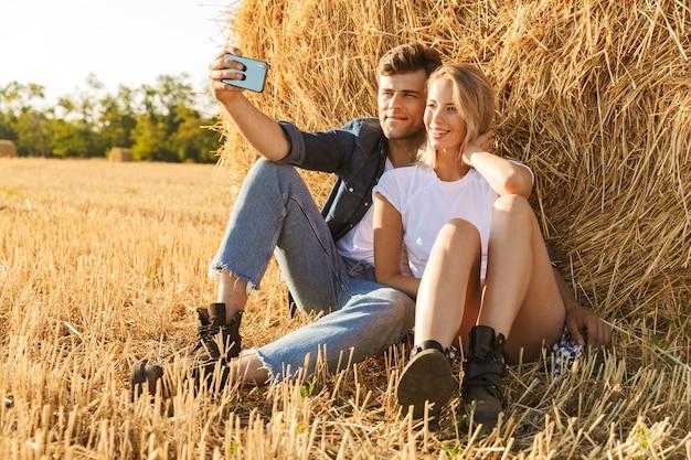 Foto van vrolijke paar man en vrouw selfie te nemen zittend onder grote hooiberg in gouden veld, tijdens zonnige dag