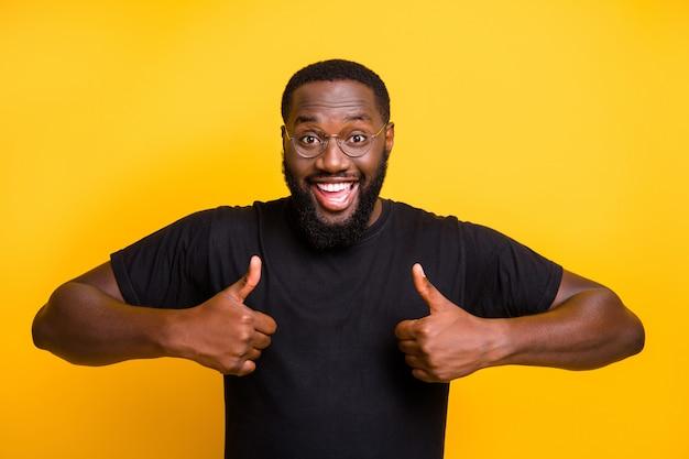 Foto van vrolijke positieve aantrekkelijke man glimlachend toothily twee duimen opdagen in t-shirt met bruin haar geïsoleerde levendige kleurenmuur