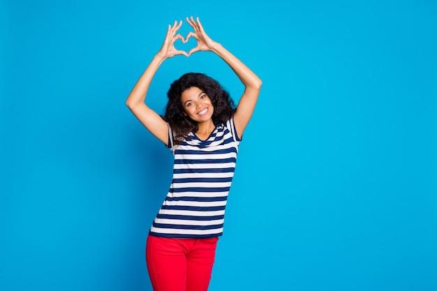 Foto van vrolijke positieve aardige vrouw die lacht die u hartteken toont