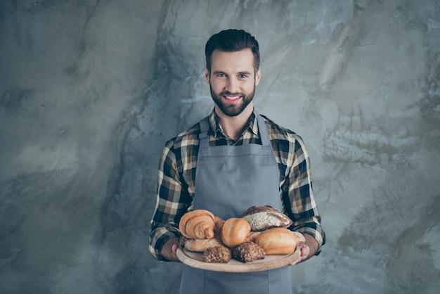 Foto van vrolijke positieve knappe aantrekkelijke chef-kok glimlachend toothily in geruit overhemd met haren geïsoleerde grijze kleur muur betonnen muur