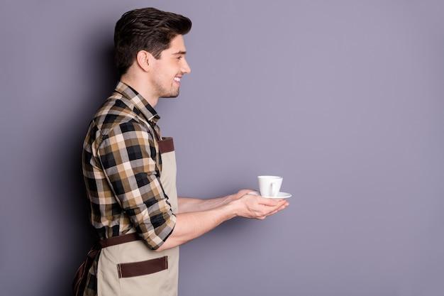 Foto van vrolijke positieve knappe aantrekkelijke man glimlachend toothy stralend portie kopje thee geven aan bezoeker geïsoleerde grijze kleur muur