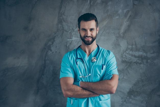 Foto van vrolijke positieve knappe dokter met gekruiste armen glimlachend toothily tonen zijn kennis op geneeskunde geïsoleerde grijze muur betonnen kleur muur