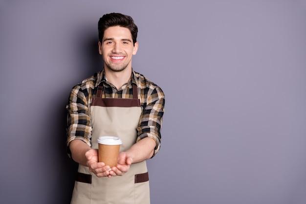 Foto van vrolijke positieve knappe man die je voorstelt om koffie te proeven uit een wegwerpbeker glimlach toothy sctretching handen geïsoleerde grijze kleur muur