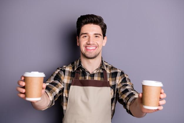 Foto van vrolijke positieve knappe man die zijn tanden in brede glimlach toont die twee kopjes koffie voor u houdt om geïsoleerde grijze kleurenmuur te kiezen