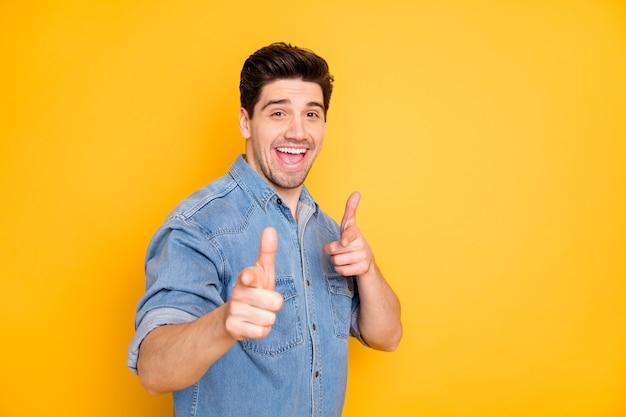 Foto van vrolijke positieve knappe man met een goed humeur die naar je wijst om je te prijzen glimlachend toothily geïsoleerde gele levendige kleurenmuur