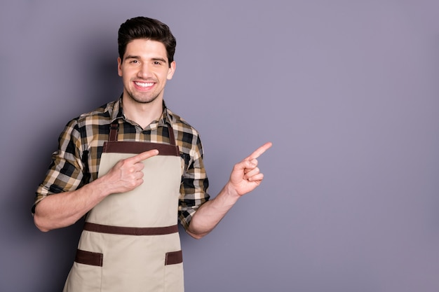 Foto van vrolijke positieve knappe man smile toothy wijzend in lege ruimte werken als barista promoing zijn café geïsoleerde grijze kleur muur