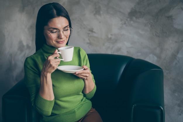 Foto van vrolijke positieve leuke mooie vrouw genieten van geur van koffie in kopje ontspannen tijdens het werk zittend in fauteuil geïsoleerde grijze betonnen kleur muur achtergrond
