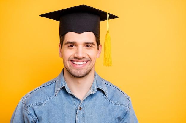 Foto van vrolijke positieve man die is afgestudeerd aan de universiteit, geïnspireerd om doelen in zijn toekomstige leven te bereiken, geïsoleerde muur in levendige kleuren